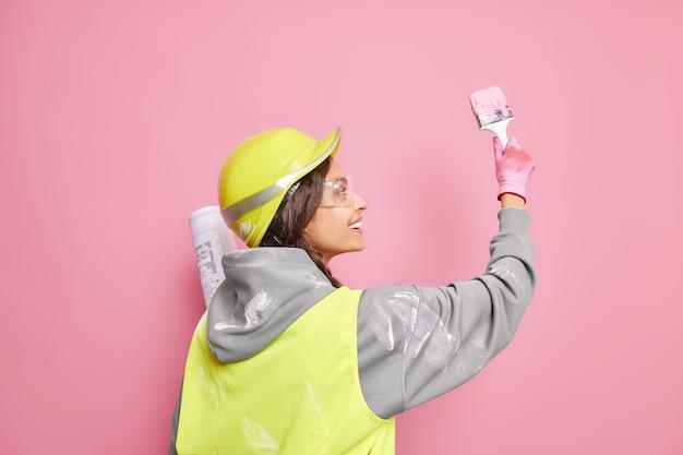 Colpo isolato di allegro abile operaio edile femminile sta indietro dipinge il muro in colore rosa usa il pennello tiene il progetto di costruzione indossa il casco e l'uniforme. servizio di manutenzione