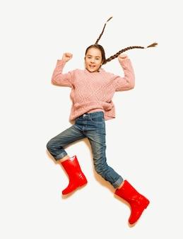 Colpo isolato di una ragazza carina sorridente con stivali di gomma rossi che salta in alto