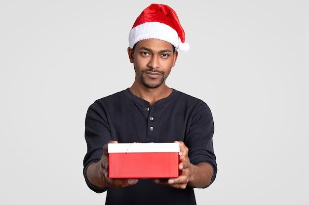 Colpo isolato di serio uomo nero indossa copricapo di babbo natale, porta piccola scatola di regalo, vestita di maglione nero