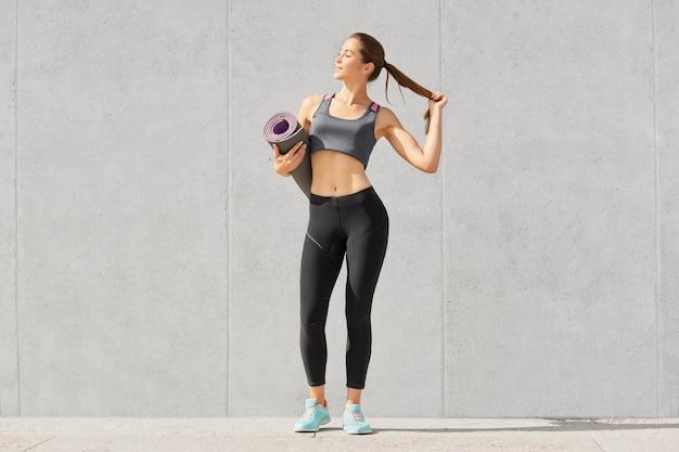 Il colpo isolato di bella sportiva esile con forma del corpo sportivo, indossa gli abiti sportivi, tiene la coda di cavallino, andando ad addestramento di forma fisica con lo strato