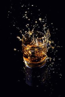 Colpo isolato di whisky con spruzzata su sfondo nero