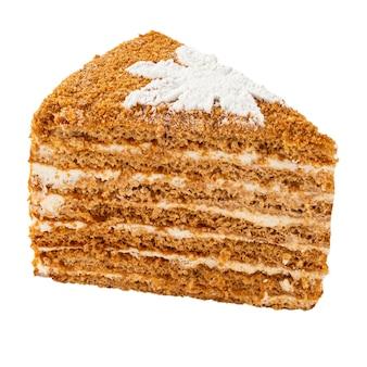 Fetta isolata di torta di miele con crema