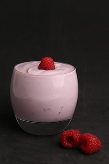 Colpo verticale isolato del primo piano di yogurt al lampone in un piatto di vetro su fondo nero