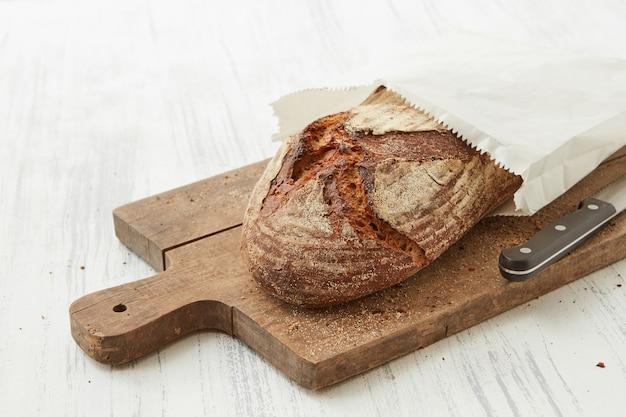 Isolato su sfondo bianco di pane in un pezzo di carta su un tagliere con un coltello
