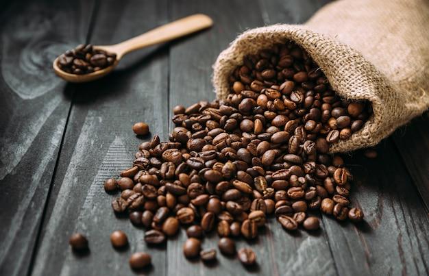 Vista isometrica della borsa della iuta con i chicchi di caffè rovesciati sulla tavola di legno