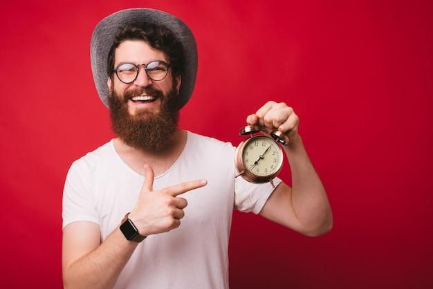È ora!!! bel ragazzo barbuto con gli occhiali con la faccia felice, con in mano un orologio vintage, su sfondo rosso