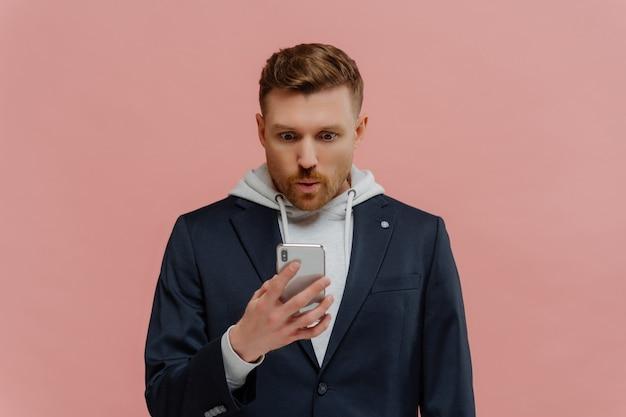 Non può essere vero. impressionato bel ragazzo dai capelli rossi con la barba in giacca sopra la felpa con cappuccio piegando le labbra in wow, leggendo notizie incredibili nel suo telefono cellulare mentre si trovava isolato sul muro rosa.