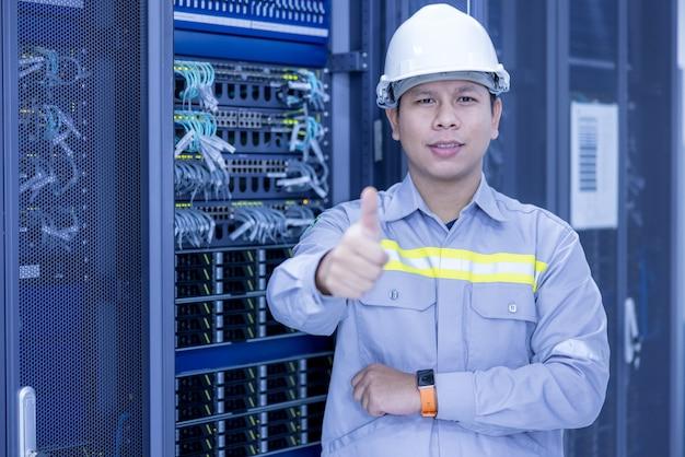 Ingegnere it in piedi e in posa con le braccia incrociate in una sala server di un data center funzionante con computer server che lavorano su un rack.