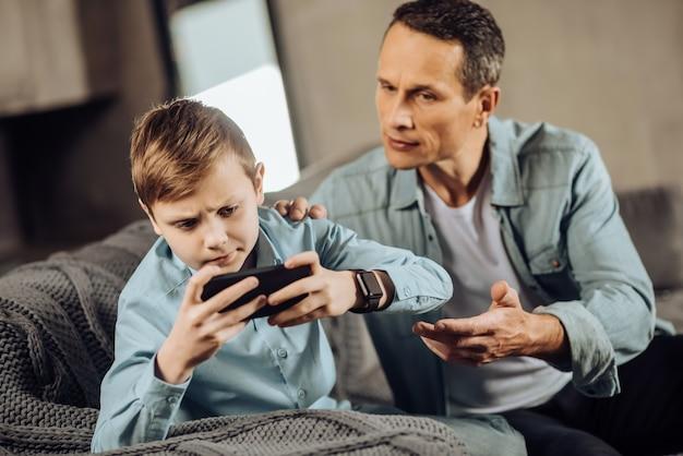 È abbastanza. rigoroso giovane padre che cerca di far smettere di giocare al telefono con suo figlio, allungando la mano e chiedendo di dargli il telefono, mentre il ragazzo è riluttante