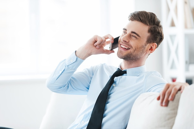 È fantastico sentirti! giovane uomo d'affari allegro che parla sul telefono cellulare e sorride