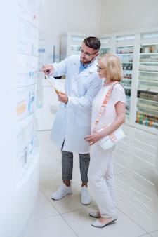 È qui. visitatore anziano concentrato in piedi vicino alla farmacia mentre sceglie le pillole necessarie