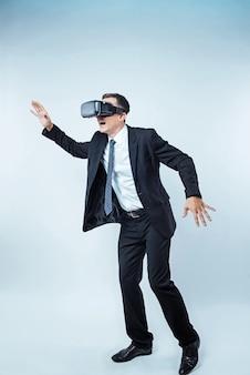 Sembra così reale. ripresa a figura intera di un impiegato che gesticola mentre viene sorpreso durante un gioco vr mentre indossa un auricolare speciale sullo sfondo.