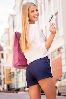 Mi facilita lo shopping. bella giovane donna dai capelli biondi che tiene le borse della spesa e guarda la telecamera con un sorriso mentre sta in piedi all'aperto
