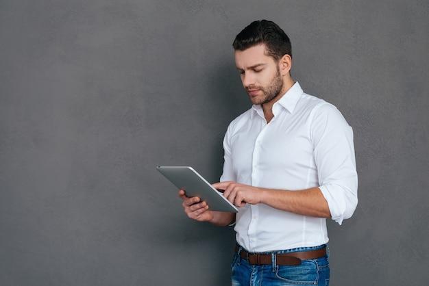 Professionista informatico. bel giovane in possesso di tablet digitale mentre in piedi su sfondo grigio