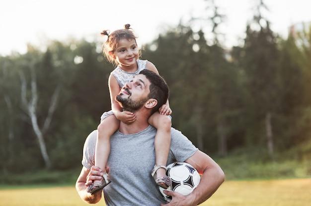Riguarda la famiglia. foto di papà con sua figlia in bella erba e boschi in background