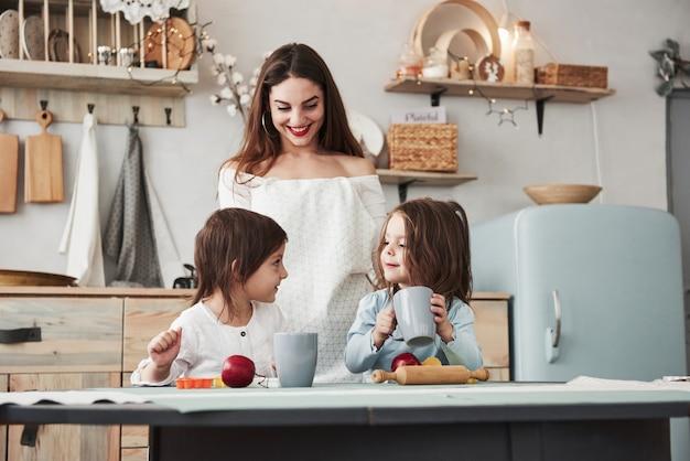 È delizioso, fidati. la giovane bella donna dà da bere ai bambini mentre sono seduti vicino al tavolo con i giocattoli.