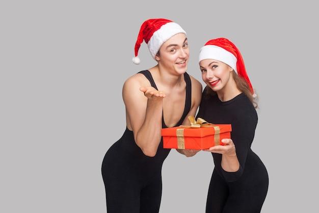 È una confezione regalo per te! coppia in cappello di natale in piedi e condivisione di confezione regalo e guardando la fotocamera. indoor, girato in studio, isolato su sfondo grigio
