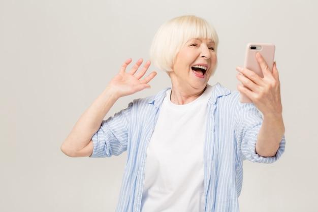È l'ora dei selfie! immagine della donna anziana matura allegra in piedi isolata sopra la parete bianca del fondo che comunica dal telefono cellulare.