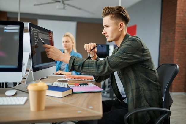 Il gruppo di specialisti it lavora ai tavoli in ufficio. programmatore web o designer sul posto di lavoro, occupazione creativa. moderna tecnologia dell'informazione, team aziendale