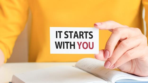 Inizia con te è scritto su un biglietto da visita bianco. la mano di una donna tiene una carta di carta bianca.