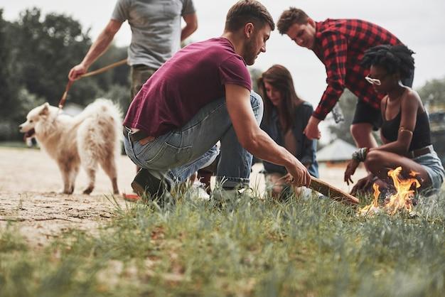 Sarà un bel fuoco da campo. un gruppo di persone fa un picnic sulla spiaggia. gli amici si divertono durante il fine settimana.
