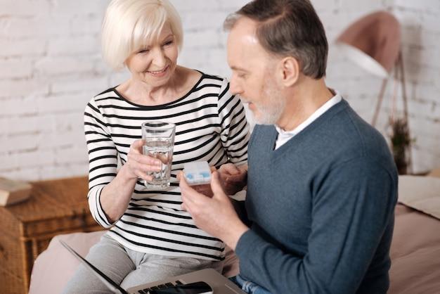 Aiuterà. la signora senior sorridente sta offrendo un bicchiere d'acqua al marito che sta per prendere le pillole.