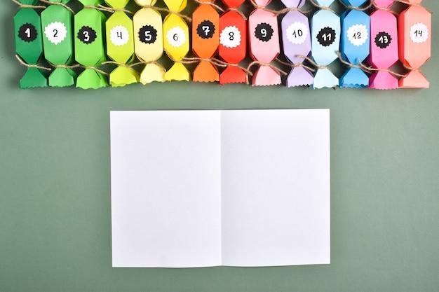 Fallo da solo. calendari dell'avvento in carta colorata a forma di dolcetti. istruzioni dettagliate passo dopo passo. artigianato di capodanno.