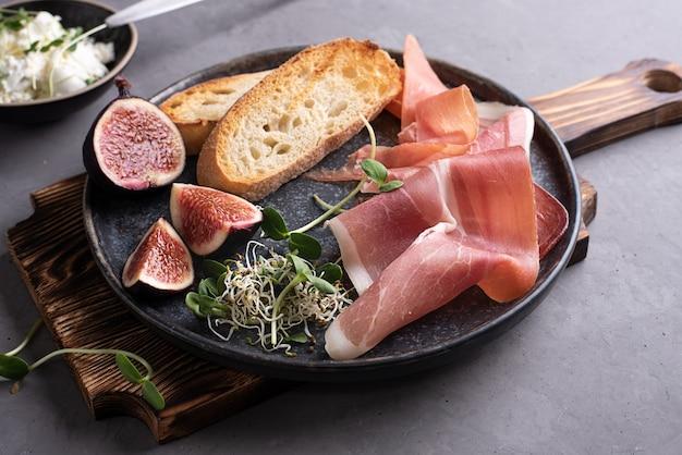 Antipasto italiano di prosciutto, pane tostato, crema di formaggio su un tagliere su sfondo grigio, snack al prosciutto.