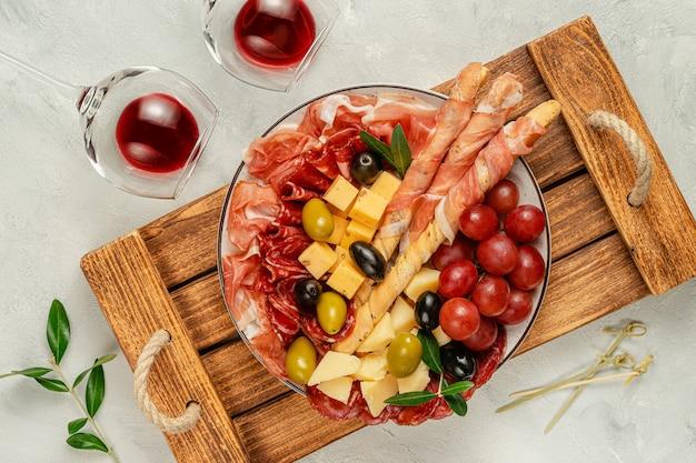 Piatto di antipasti italiani con prosciutto grissini, olive e formaggio sul vassoio in legno