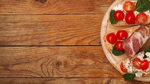 Bruschetta antipasto italiano su una tavola di legno su una superficie rustica in legno