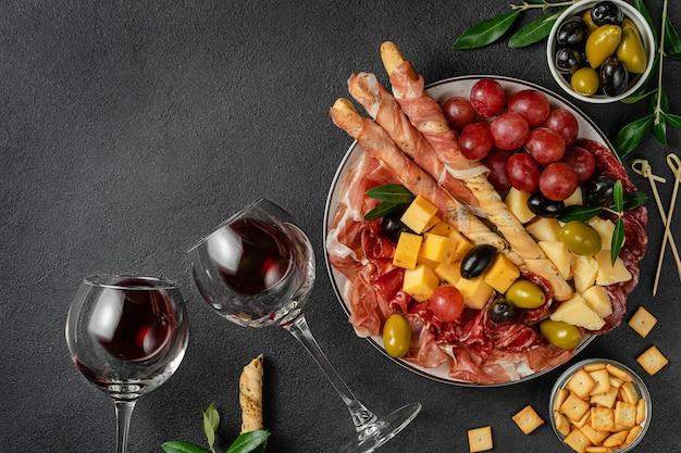 Piatto di antipasti italiani con vino sulla superficie scura