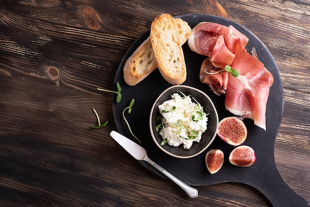 Antipasto italiano, prosciutto con frutta e formaggio, prosciutto crudo con fette di pane su uno sfondo di legno scuro.