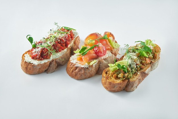 Antipasto italiano - tre bruschette con pomodori, salmone e peperoni al forno su uno sfondo bianco