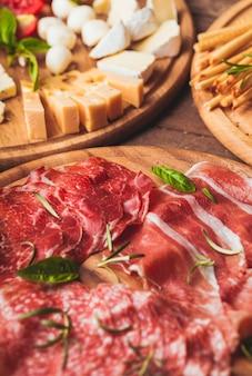 Antipasto italiano - vari tipi di prosciutto, formaggio e grissini