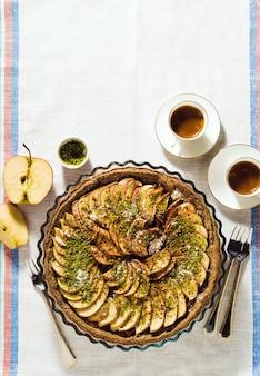 Torta di mele italiana crostata con granella di pistacchio sul tavolo con una tovaglia bianca e tazze di caffè espresso