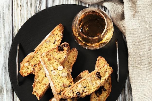 Biscotti italiani di biscotti sul bordo nero dell'ardesia e sul vino dolce vin santo fresh