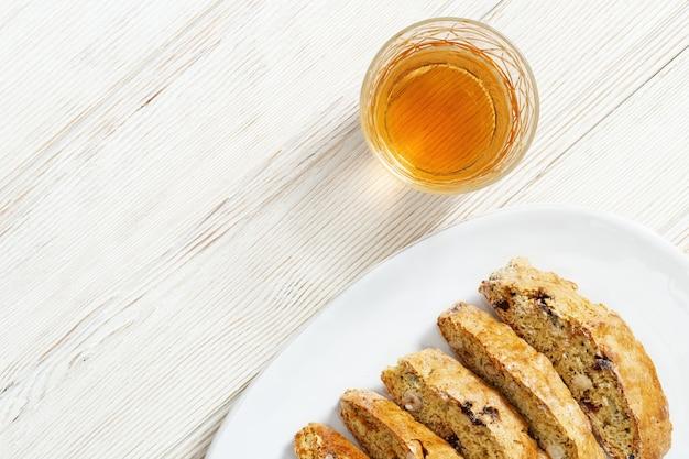 Biscotti italiani di biscotti in piatto bianco e vino dolce vin santo.