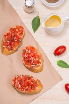 Bruschetta italiana con pomodori arrostiti, mozzarella ed erbe aromatiche su carta