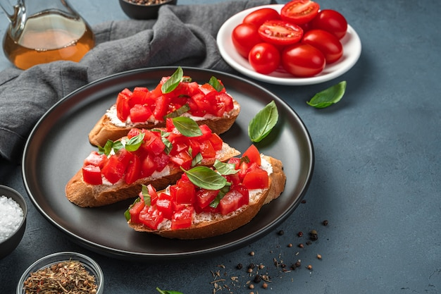 Bruschetta italiana con pomodoro, basilico e formaggio su sfondo grigio-blu. vista laterale, spazio per la copia.