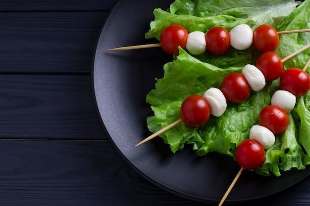 Insalata caprese italiana con palline di mozzarella e pomodori allo spiedo.