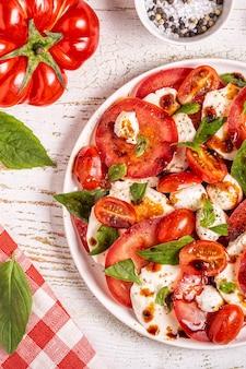 Insalata caprese italiana con pomodori a fette, mozzarella, basilico, olio d'oliva, aceto balsamico. vista dall'alto, copia dello spazio.