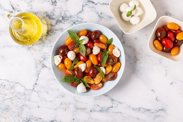 Insalata caprese italiana con pomodori, mozzarella, basilico, olio d'oliva, vista dall'alto.