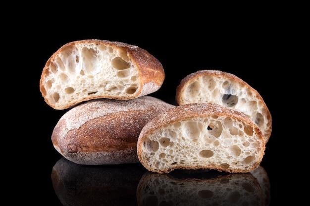 Pane a fette di ciabatta italiana. pane fatto in casa appena sfornato isolato sul nero. mangiare sano e panetteria tradizionale, concetto di pane da forno.