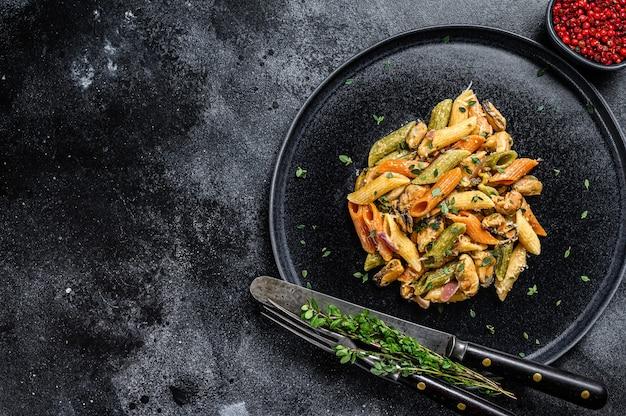 Pasta italiana di colore penne con le cozze su un piatto. sfondo nero. vista dall'alto. copia spazio.
