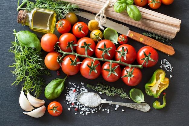 Ingredienti della cucina italiana: pomodorini, erbe aromatiche, pasta e olio d'oliva su uno sfondo scuro