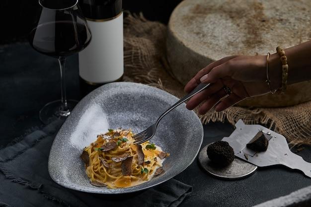 Spaghetti della cucina italiana con tartufo nero su un piatto grigio e una bottiglia di vino messa a fuoco selettiva verticale