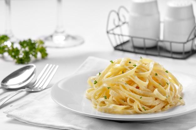 Cucina italiana tagliatelle alla carbonara su semplice piatto bianco