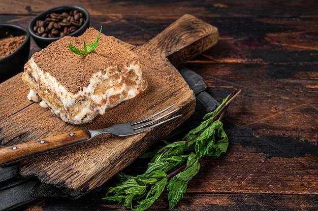 Dolce italiano tiramisù con cacao e menta su una tavola di legno. fondo di legno scuro. vista dall'alto. copia spazio.