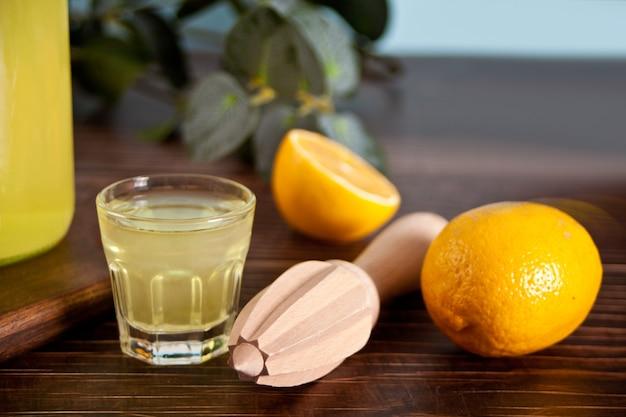 Bevanda italiana liquore al limone limoncello in vetro sul tavolo di legno con bottiglia e frutta al limone
