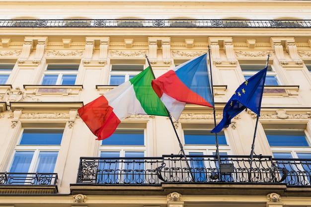Bandiere italiane ed europee e altra bandiera su un balcone.